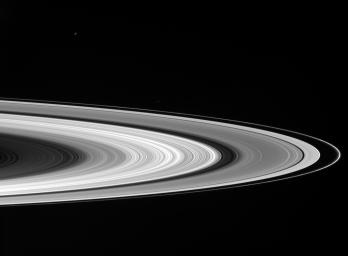 Saturn's sunlit rings gleam in the blackness as two icy moons cruise past in the foreground