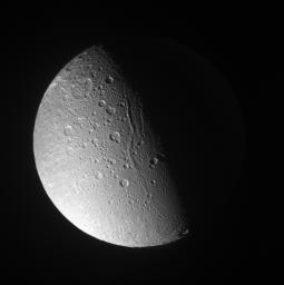 Canyons and mountain peaks snake along the terminator on the crater-covered, icy moon Dione. With the Sun at a low angle on their local horizon, the line of mountain ridges above center casts shadows toward the east