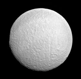 Ithaca Chasma rips across Saturn's moon Tethys from north to south near the center of this view from NASA's Cassini spacecraft. The moon's western limb is flattened, indicating the rim of the giant impact basin Odysseus.
