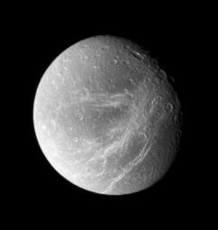 Bright, wispy fractures streak across Saturn's moon Dione's trailing side. This image was taken in visible light with NASA's Cassini spacecraft's wide-angle camera on Sept. 30, 2007.