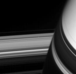 A small ring-embedded moon coasts into view from behind shadow-draped Saturn. The rings' image is distorted near Saturn by the planet's upper atmosphere, to the right of Pan, as viewed by NASA's Cassini spacecraft on Dec. 22, 2007.