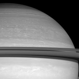 Two small moons, Janus and Pandora, race across the face of Saturn. The planet's icy rings cast dark shadows onto the feathery clouds below in this image captured by NASA's Cassini spacecraft on June 18, 2008.