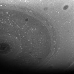 Myriad dark vortices, some large and some small, twirl in the high southern latitudes of Saturn. At left, the south polar vortex spins at the center of it all. This image was taken with NASA's Cassini spacecraft's wide-angle camera on June 23, 2008.