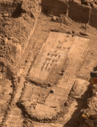 NASA's Phoenix Mars Lander used the motorized rasp on the back of its robotic arm scoop on July 26, 2008 to penetrate a hard layer at the bottom of a trench informally called Snow White.This image shows most of the 16 holes left by a four-by-four array.