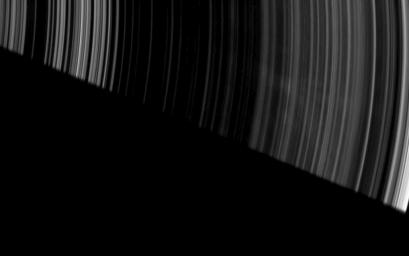 Faint, ghostly spokes dapple the dark side of Saturn's A ring as the planet's shadow makes a sharp diagonal cut across this image from the Cassini spacecraft.