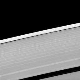 A scalloped look is created in the edges of the Keeler Gap in Saturn's outer A ring as the moon Daphnis orbits in the gap.