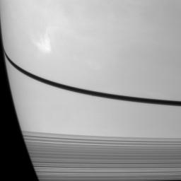 NASA's Cassini Orbiter caught the shadow of the moon Prometheus as a small dark dot on Saturn just below the narrow shadow cast by the rings in the center of this image.