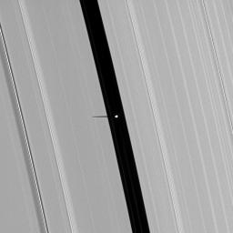 Saturn's small moon Pan, brightly overexposed, casts a short shadow on the A ring in this image taken by NASA's Cassini spacecraft before the planet's August 2009 equinox.