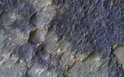 In this image from NASA's Mars Reconnaissance Orbiter is an old degraded crater that has undergone a complex history of burial and erosion. At least two types of exposed bedrock are shown here.