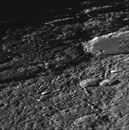 NASA's Mariner 10 shows a close-up view of craters Vyasa and Stravinsky on Mercury. Stravinsky is a smooth-floored crater partially seen overlying the rim of the larger, rougher crater Vyasa in the center and left.