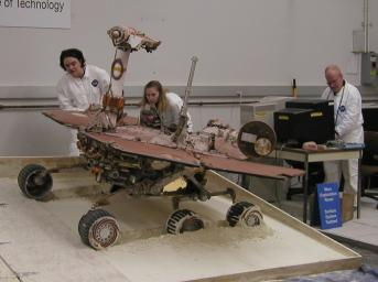 While a test rover rolls off a plywood surface into a prepared bed of soft  soil, rover team members Colette Lohr (left) and Kim Lichtenberg (center)  eye the wheels digging into the soil and Paolo Bellutta enters the next  driving command.