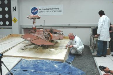 After commanding five of a test rover's six wheels to drive forward, rover driver Paolo Bellutta (left) measures how much the rover moved sideways, downslope, during the maneuver.