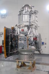 NASA's Wide-field Infrared Survey Explorer spacecraft is situated on a work stand. At left on the spacecraft is the fixed panel solar array. In front, the square is the HGA Slotted Array (Ku-Band).