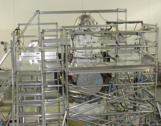 A scaffolding structure built around NASA's Wide-field Infrared Survey Explorer allows engineers to freeze its hydrogen coolant. The WISE infrared instrument is kept extremely cold by a bottle-like tank filled with frozen hydrogen, called the cryostat.