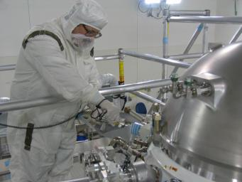 An engineer loads hydrogen gas into the Wide-Field Infrared Survey Explorer in a clean room at the Vandenberg Air Force Base, Calif. The hydrogen is cooled and frozen inside a Thermos-like bottle, called the cryostat, which keeps the science instrument