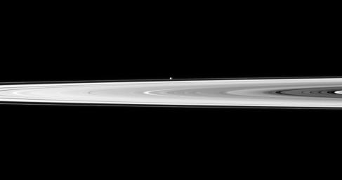 The tiny moon Pandora appears beyond the bright disk of Saturn's rings in this image taken by NASA's Cassini spacecraft. Pandora orbits outside the F ring and, in this image, is farther from Cassini than the rings are.