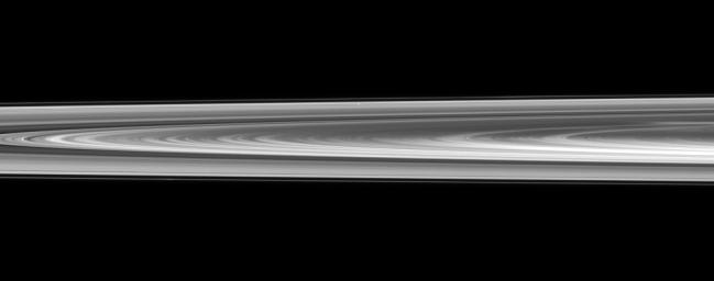 Pan is nearly lost within Saturn's rings in this view captured by NASA's Cassini spacecraft of a small section of the rings from just above the ringplane.
