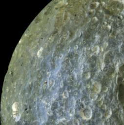 A false-color view of Saturn's moon Mimas from NASA's Cassini spacecraft accentuates terrain-dependent color differences and shows dark streaks running down the sides of some of the craters on the region of the moon that leads in its orbit around Saturn.