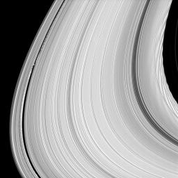 This image taken by NASA's Cassini spacecraft shows that rather than being an unchanging disk of peaceful particles, the material that makes up Saturn's rings is constantly pushed and pulled into spectacular shapes. At left is the moon Daphnis.