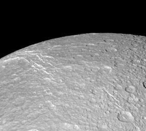 NASA's Cassini spacecraft looks across the surface of Saturn's moon Dione and details the 'wispy' terrain first chronicled by Voyager. This fractured terrain covers the trailing hemisphere of Dione.