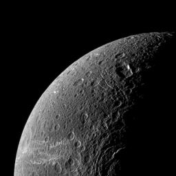 Wispy terrain reflects sunlight brightly in the lower left of this NASA Cassini image of the northern latitudes of Saturn's moon Dione.