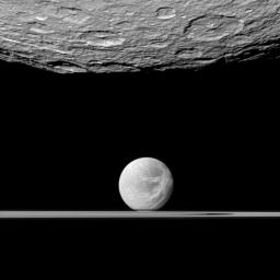 NASA's Cassini spacecraft looks past the cratered south polar area of Saturn's moon Rhea to spy the moon Dione and the planet's rings in the distance. Dione's 'wispy' terrain can be seen on the trailing hemisphere of that moon.