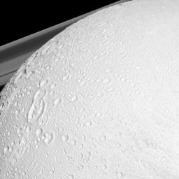 NASA's Cassini spacecraft watches over the northern latitudes of Saturn's geologically active moon Enceladus while the planet's rings peek through in the distance in this snapshot.