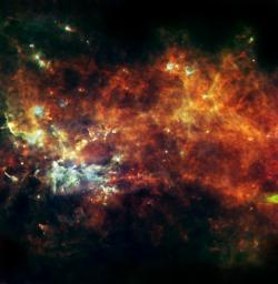 This image from NASA's Herschel, in the constellation of Vulpecula, shows an entire assembly line of newborn stars. The diffuse glow reveals the widespread cold reservoir of raw material that our Milky Way galaxy has in stock for building stars.