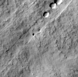 This image captured by NASA's Mars Odyssey orbiter shows a Martian pit feature on the slope of an equatorial volcano named Pavonis Mons, appears to be a skylight in an underground lava tube.
