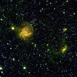A star-forming region shines from the considerable distance of more than 30,000 light-years away in the upper left of this image from NASA's Spitzer Space Telescope. This image is a combination of data from Spitzer and the Two Micron All Sky Survey.