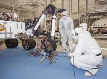Test operators in a clean room at NASA's Jet Propulsion Laboratory monitor some of the first motions by the robotic arm on the Mars rover Curiosity after installation in August 2010. The arm is shown in a partially extended position.