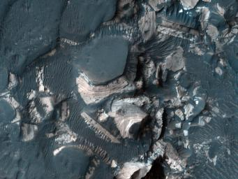 This image from NASA's Mars Reconnaissance Orbiter shows blocks of bright, layered rock embedded in darker material that are thought to have been deposited by a giant flood that occurred when Uzboi Valles breached the rim of Holden Crater.