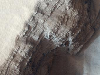 This observance from NASA's Mars Reconnaissance Orbiter covers a pit in the lower West flank of Arsia Mons, one of the four giant volcanos of the Tharsis region. Many layers are exposed in the pit, probably marking individual lava flows.