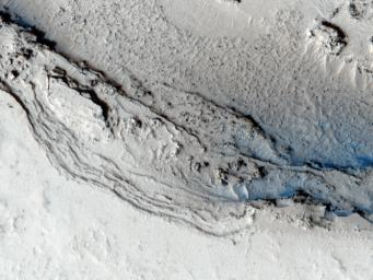 This image from NASA's Mars Reconnaissance Orbiter shows the funnel-shaped terminus of Lethe Vallis, a winding channel in the Elysium Planitia region of Mars; the floor is covered in solidified lava and blanketed by a thin layer of light-toned dust.