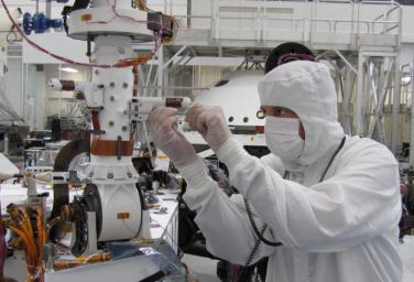 Sensors on two finger-like mini-booms extending horizontally from the mast of NASA's Mars rover Curiosity will monitor wind speed, wind direction and air temperature; image taken during installation of the instrument inside a clean room at NASA's JPL.