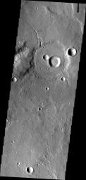 This image from NASA's Mars Odyssey shows a small unnamed channel entering and running along the rim of this unnamed crater in Arabia Terra.