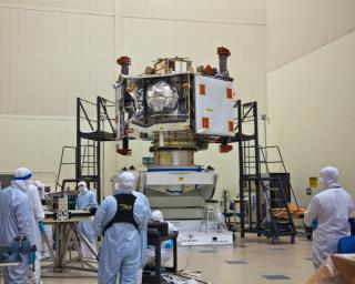 NASA's Juno spacecraft rests atop its rotation fixture awaiting transfer to a shipping crate prior to environmental testing; the large white square on the spacecraft's right is largest of six microwave radiometer antennas, masked by protective covering.