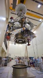 Technicians transfer NASA's Juno spacecraft from its rotation fixture to the base of its shipping container in preparation for a move to environmental testing facilities. Juno�s main engine, its cover closed, is visible on the spacecraft�s underside.