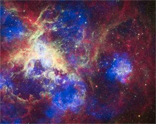 This composite of 30 Doradus, the Tarantula Nebula, contains data from Chandra (blue), Hubble (green), and Spitzer (red). Located in the Large Magellanic Cloud, the Tarantula Nebula is one of the largest star-forming regions close to the Milky Way.