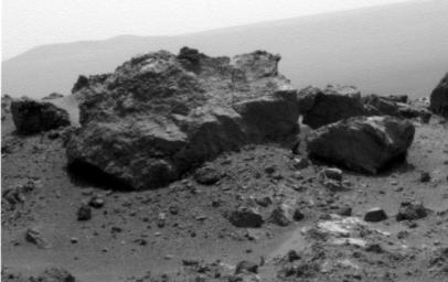This view from NASA's Mars Exploration Rover Opportunit is dominated by a rock informally named 'Ridout' on the northeastern rim of Odyssey. The rock is roughly the same size as the rover, 4.9 feet (1.5 meters) long.