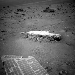 Part of NASA's Mars Exploration Rover Opportunity's array of photovoltaic cells is visible in the foreground of this image. Opportunity took this picture showing a light-toned rock, 'Tisdale 2,' on sol 2,690 (Aug. 18, 2011).