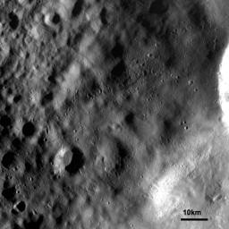 This image from NASA's Dawn spacecraft shows an ejecta blanket mantling the surface and obscuring older caters. The bright crater rim, seen in the middle right edge, is one of a group of craters which are the source of this ejecta blanket.