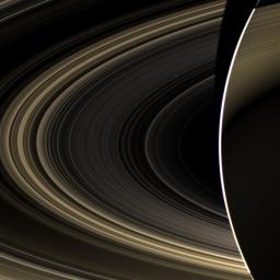 Peering over the shoulder of giant Saturn, through its rings, and across interplanetary space, NASA's Cassini spacecraft spies the bright, cloudy terrestrial planet, Venus.