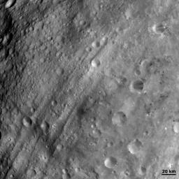 Equatorial troughs of asteroid Vesta are shown running obliquely across this image from NASA's Dawn spacecraft. The troughs both overlie and are overlain by impact craters.