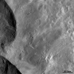 This image from NASA's Dawn spacecraft shows ejecta from two of the large 'Snowman' craters on the left of the image. This ejecta smooths out asteroid Vesta's surface in the rest of the image.