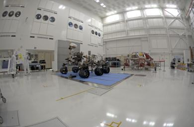 Left-eye view of NASA's Curiosity rover and its powered descent vehicle pose for photographs prior to being integrated for launch at JPL's Spacecraft Assembly Facility.