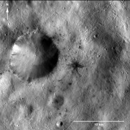 This image of a dark-rayed impact crater and several dark spots was obtained by NASA's Dawn spacecraft. The dark materials are located near an older, larger crater in the Sextilia quadrangle of asteroid Vesta's southern hemisphere.