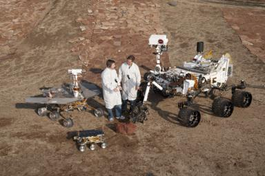 Two spacecraft engineers stand with three generations of Mars rovers developed at NASA's JPL, Pasadena, Ca. Front and center is a flight spare of Sojourner, left is a working sibling to Spirit and Opportunity, right is test rover Curiosity.