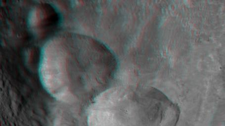This anaglyph shows the topography of Vesta's 'Snowman' craters on asteroid Vesta. The bottom crater is named Marcia, the middle crater, Calpurnia, and the top crater, Minucia. You need 3-D glasses to view this image.
