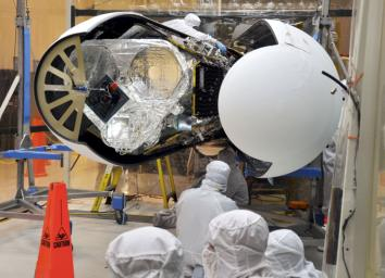 An Orbital Sciences technician completes final checks of NASA's Nuclear Spectroscopic Telescope Array, or NuSTAR, before the Pegasus payload fairing is secured around it.